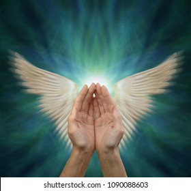 Sending out Angelic Healing Energy - cupped female hands with motion blurred angel wings either side on a blue green  background with copy space above