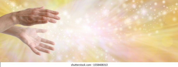 Sending out beautiful golden healing energy - female hands with sparkling white light flowing outwards against a wide golden orange yellow flowing energy background with copy space