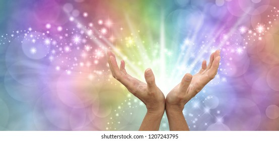Sending out beautiful powerful white light healing energy - pair of open hands facing up with white energy beaming outwards against a sparkling rainbow coloured background