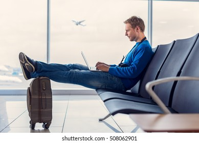 Sending quick text before take-off. Handsome young man sitting at airport and enjoying his laptop while waiting landing