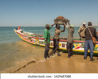 Senegal, Africa - January 24, 2019: Fishermen carries box with shells fished out of the ocean. Africa