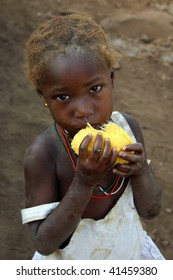 SENEGAL - FEBRUARY 15: Bedic ethnic girl posing while eating fruit, are an ethnic minority Bedic located in the country Bassari, February 15, 2007 in Kedougou, Country Bassari,Senegal