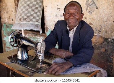 SENGA BAY, MALAWI - JUNE 10, 2018: Unidentified taylor with a sewing machine in a small village near Senga Bay. Malawi is one of the poorest countries in the world.