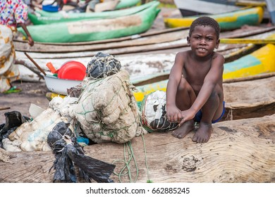 SENGA BAY, MALAWI - SEPTEMBER 05 2009: An African boy sits on his Mokoro at Senga Bay on Lake Malawi. Mokoro are dug-out canoes used for fishing and transport on Lake Malawi.