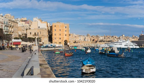 Senglea, Malta - March 7 2017: Senglea seafront  with traditional fishing boats and yachts by sunny day overlooking skyline of Valletta