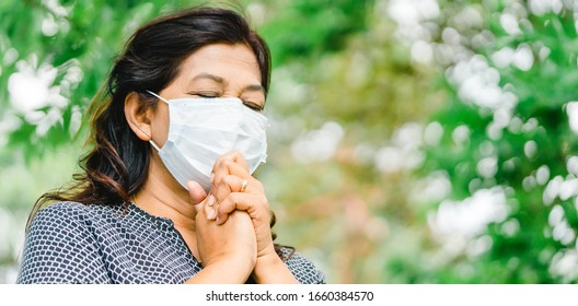 Senior 58 years old indian - iran woman wearing mask for protect pm2.5 and Covid-19.She praying in the morning for a new day freedom to Covid19 virus.Old woman hand praying for thank GOD.Copy space.