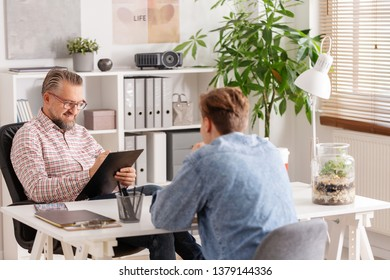Senior account manager and young man during job interview in small firm