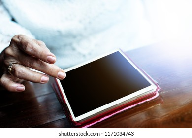 Senior adult aging retire elderly woman chat texting with friend, family, play game, reading on dining table relax and socialize using tablet, ipad, internet online digital technology to communicate