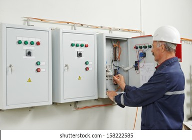 senior adult electrician builder engineer testing equipment in fuse box