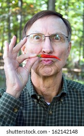 Senior adult holds a red chili pepper under his nose in a mustache position with a silly look on his face.