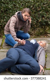 senior adult is lying on the ground, young woman makes an emergency call