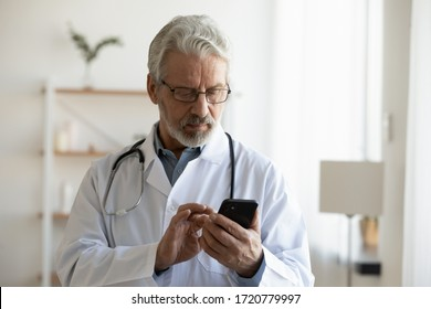 Senior adult male doctor holding smart phone using remote medical consultation applications, texting messages, chatting with distance patient online using telemedicine mobile app standing in hospital.