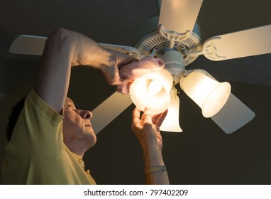 Senior adult male dusting the glass shade of a bulb in a ceiling fan and lighting fixture