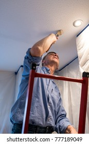 Senior adult male on ladder painting the ceiling of a room inside his home