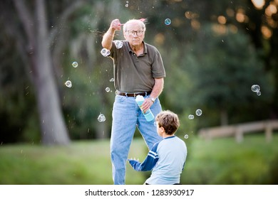 Senior adult man making bubbles for his young grandson outside at sunset.