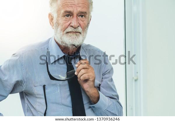 Senior adult man portrait holding eyeglasses in his hand.