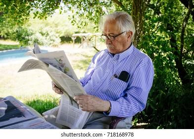 Senior adult man reading newspaper in the garden.