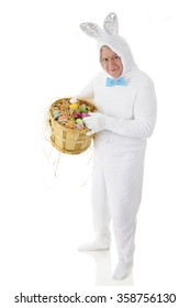 A senior adult man in a white bunny costume happily showing off his bushel basket full of colored eggs.  On a white background.