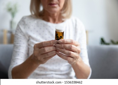 Senior adult mature woman read drug medicine prescription label, ill sick middle aged old grandma hold bottle take pills tablets worried about side effect, close up view, pharmacy healthcare concept