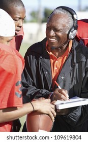 Senior African American coach with football players noting down score in book