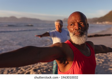 Senior african american couple performing stretching exercise together at the beach. fitness yoga and healthy lifestyle concept