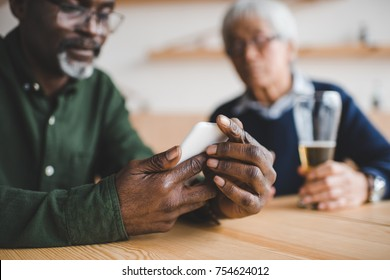 senior african american man using smartphone while spending time with friend at bar