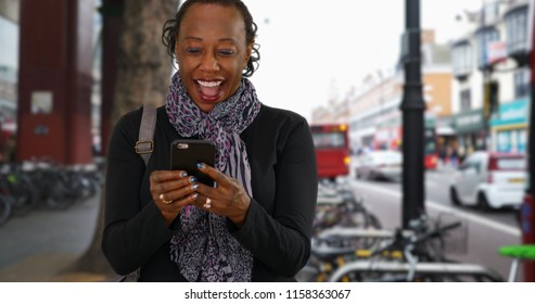 Senior African American woman laughs at funny text on London street