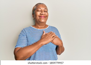 Senior african american woman wearing casual clothes smiling with hands on chest, eyes closed with grateful gesture on face. health concept.