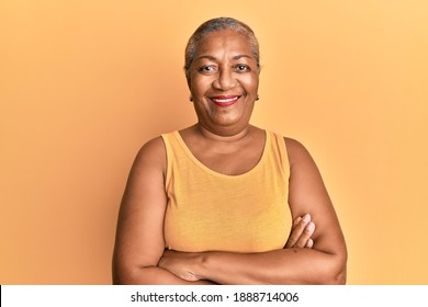 Senior african american woman wearing casual style with sleeveless shirt happy face smiling with crossed arms looking at the camera. positive person.