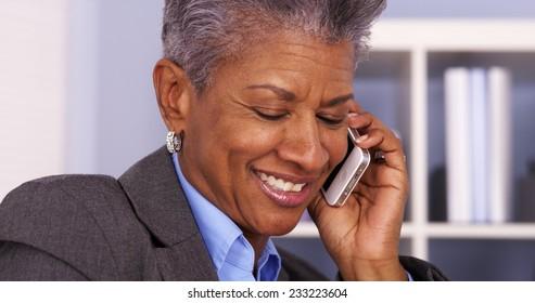 Senior African businesswoman talking on smartphone