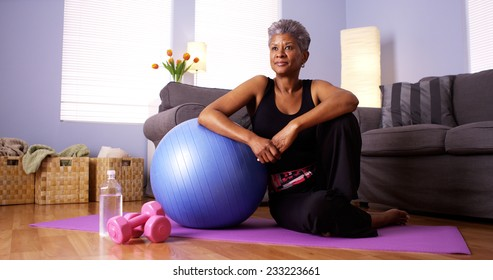 Senior African woman sitting on floor with exercise equipment