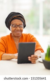senior african woman using tablet computer at home