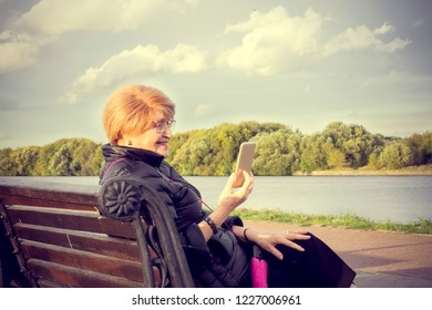 Senior age woman walk and look at smartphone
