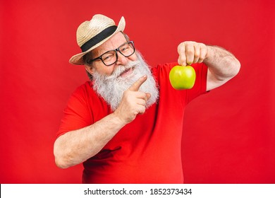 Senior aged old man having a green apple isolated on red background. Health concept.