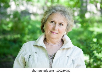 Senior aged woman outdoors in park thinking and reflecting