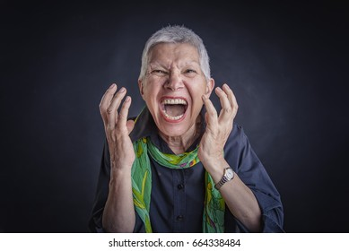 Senior angry enraged woman yelling, pissed off, black background