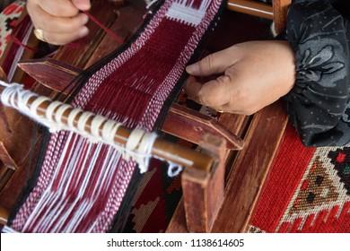 A senior arabian woman makes a traditional sadu weaving. Hands of a weaver close-up, focus on the hand. Qatar