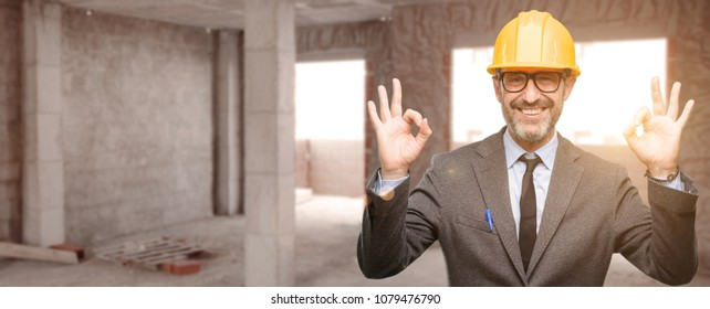 Senior architect or engineer doing ok sign gesture with both hands expressing meditation and relaxation at unfinished building