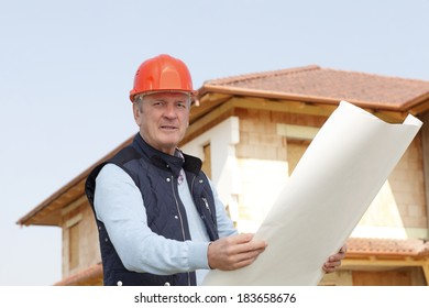 Senior architect standing in front of building. Small business.