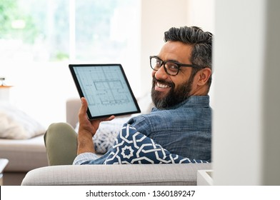 Senior architect working on blueprint for client on digital tablet while relaxing at home. Rear view of architect drawing blueprint on digital tablet using software while lying on couch.