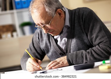 Senior architect working on construction blueprint in office, he draws with a pencil and ruler.