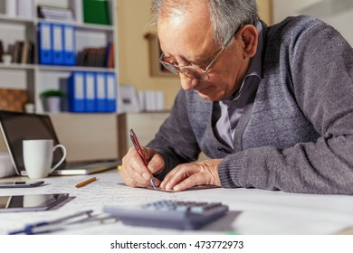 Senior architect working on construction blueprint in office.