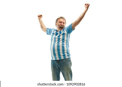 The senior Argentinean fan celebrating on white background. The mature man in soccer football uniform as winner isolated at white studio. Fan, support concept. Human emotions concept.