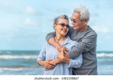 Senior asia couple relaxing by the sea on sunny day