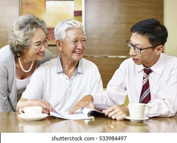 senior asian couple listening to a sale representative, happy and smiling