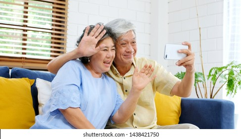 Senior asian couple make video call to family, friend smiling with happiness while sitting at sofa in home living room, old people and technology lifestyle, active senior retirement