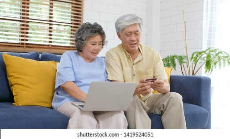 Senior asian couple shopping online by using laptop computer and credit card at home living room, Retirement people technology lifestyle
