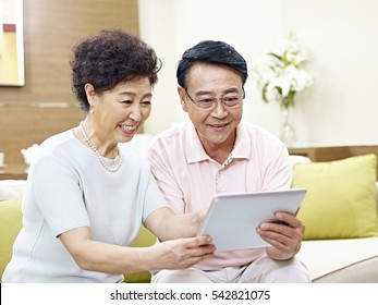 senior asian couple sitting on couch looking at tablet computer together, happy and smiling