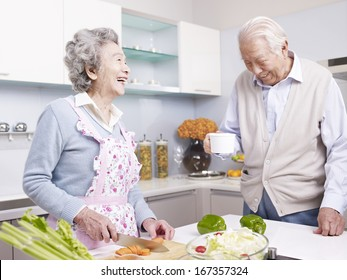 senior asian couple talking and laughing in kitchen.
