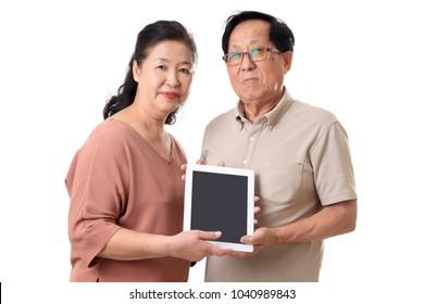 The senior Asian couple using tablet on the whitebackground.